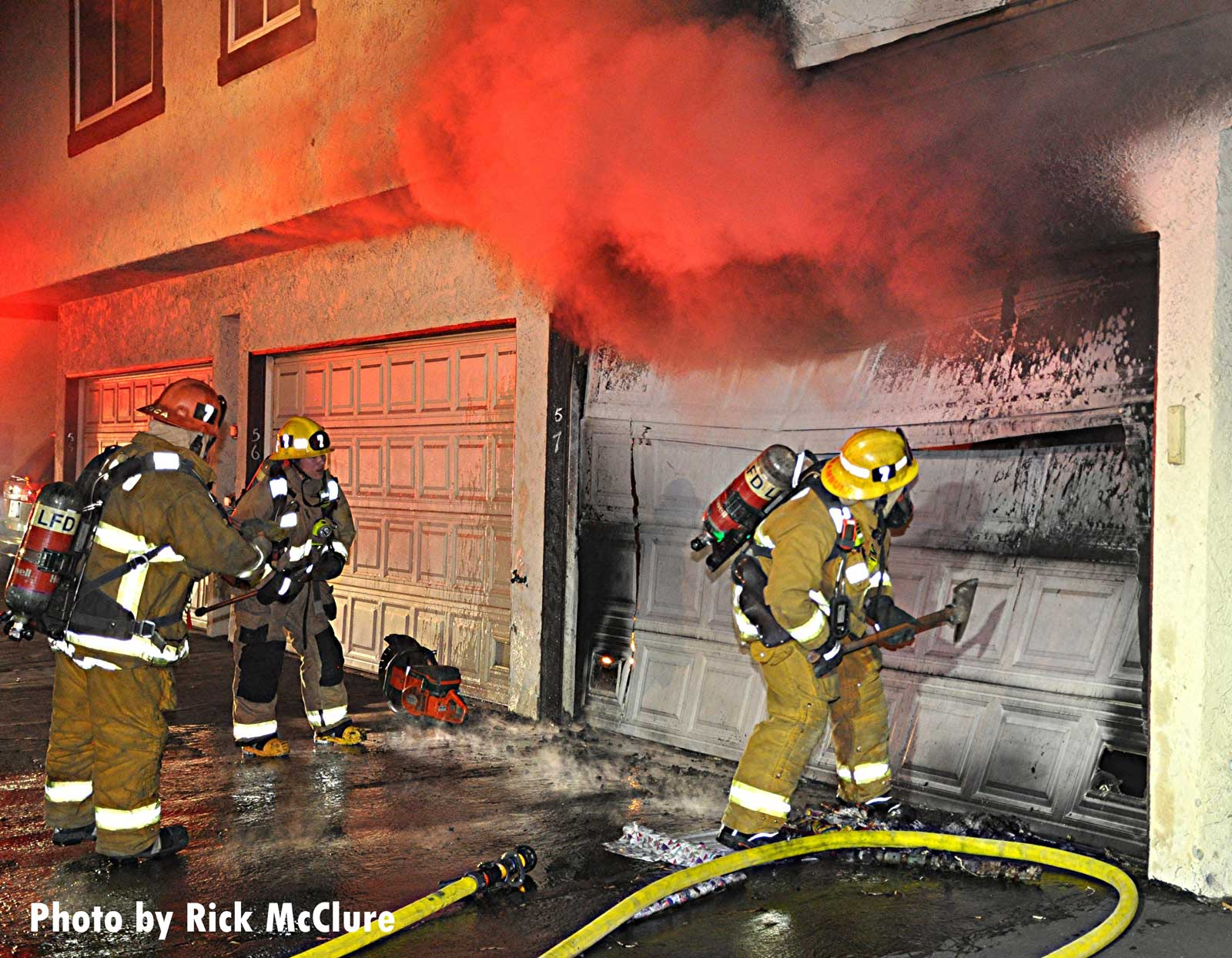 Smoke shoots from a garage as an LAFD firefighter attempts to gain entry