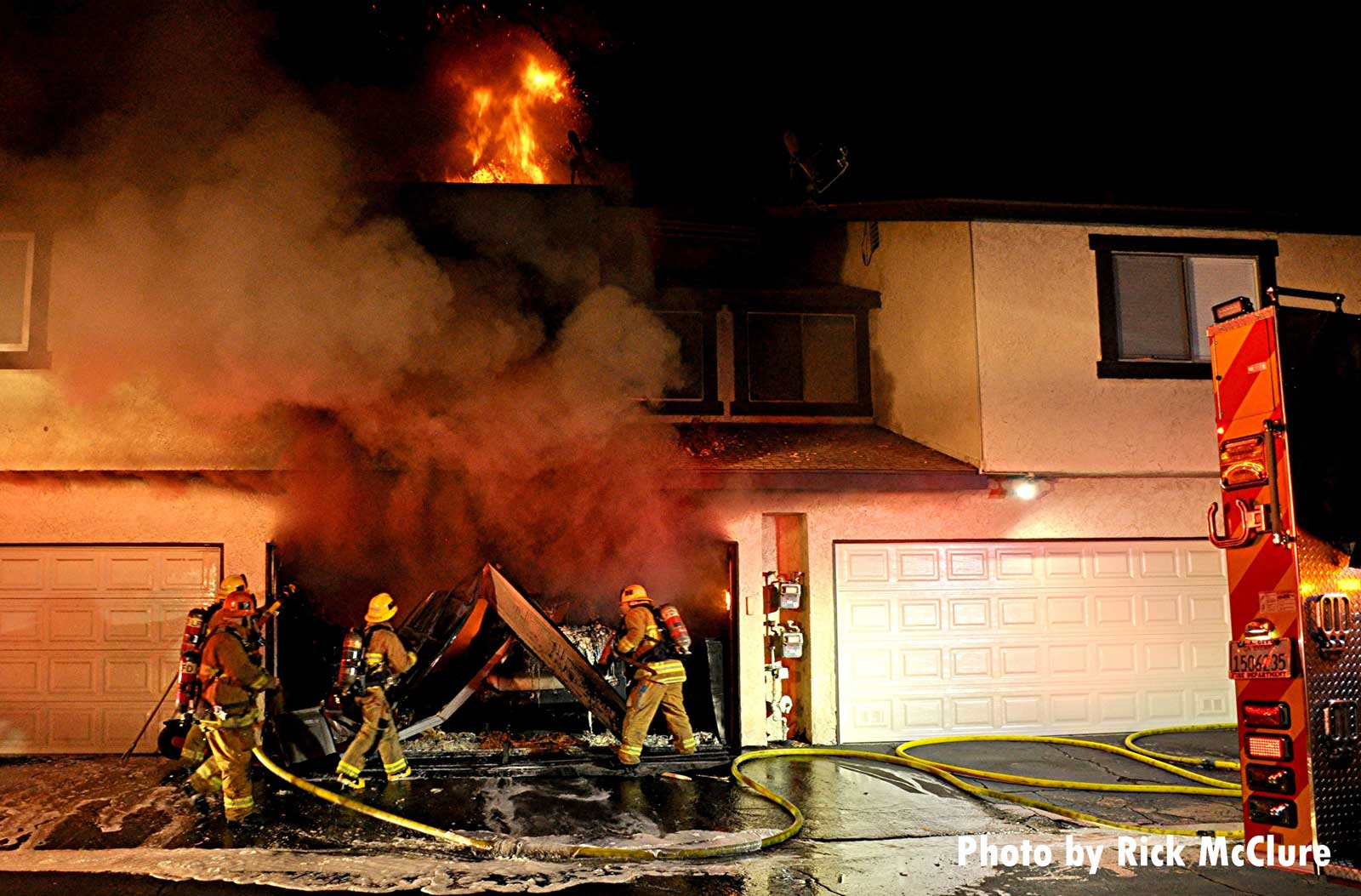 Firefighters on a hoseline put water in the garage as flames vent from a room above