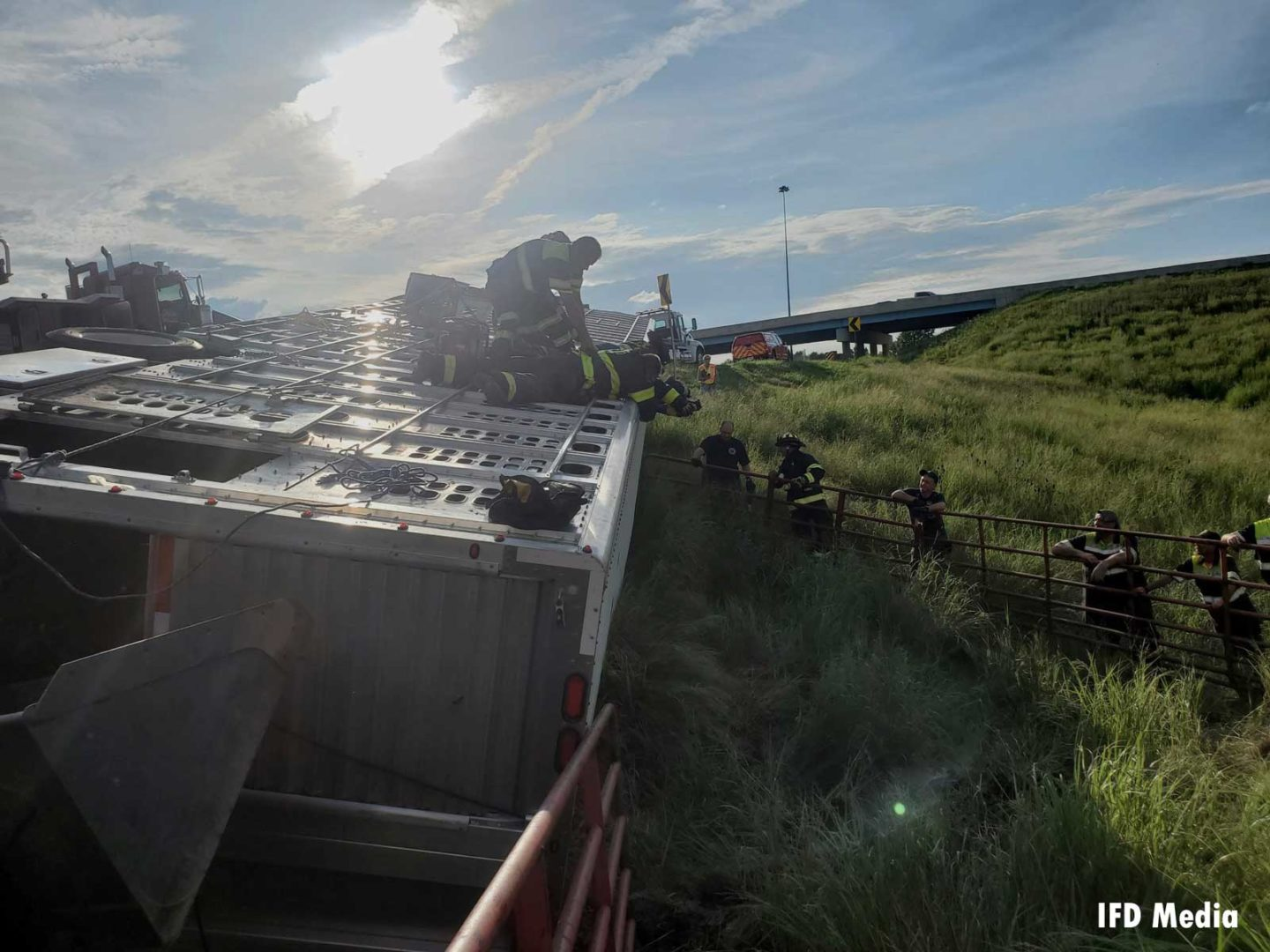Firefighters work on the roof of the overturned trailer