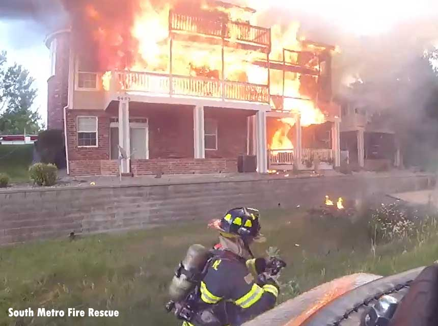 Firefighters pull lines at a town home fire in Lone Tree