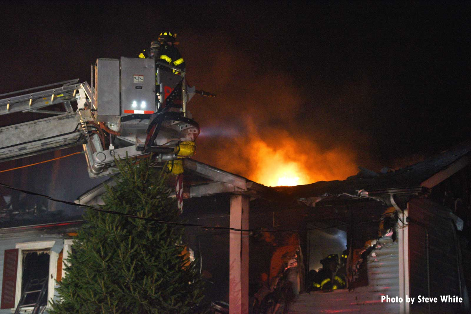 FDNY Tower Ladder with fire showing from roof of dwelling