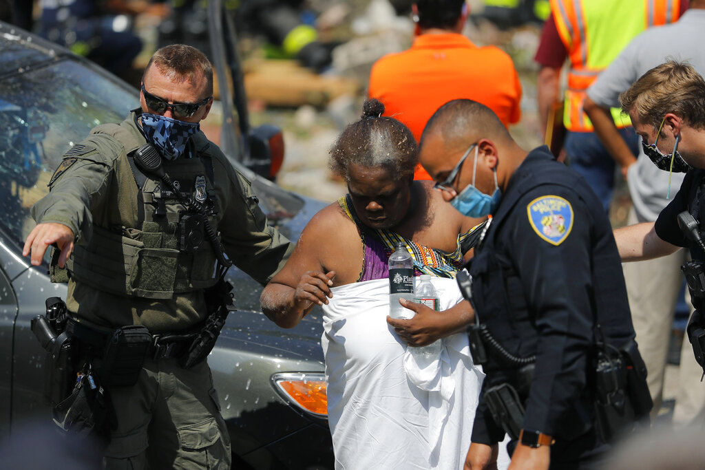 Authorities guide a person after an explosion