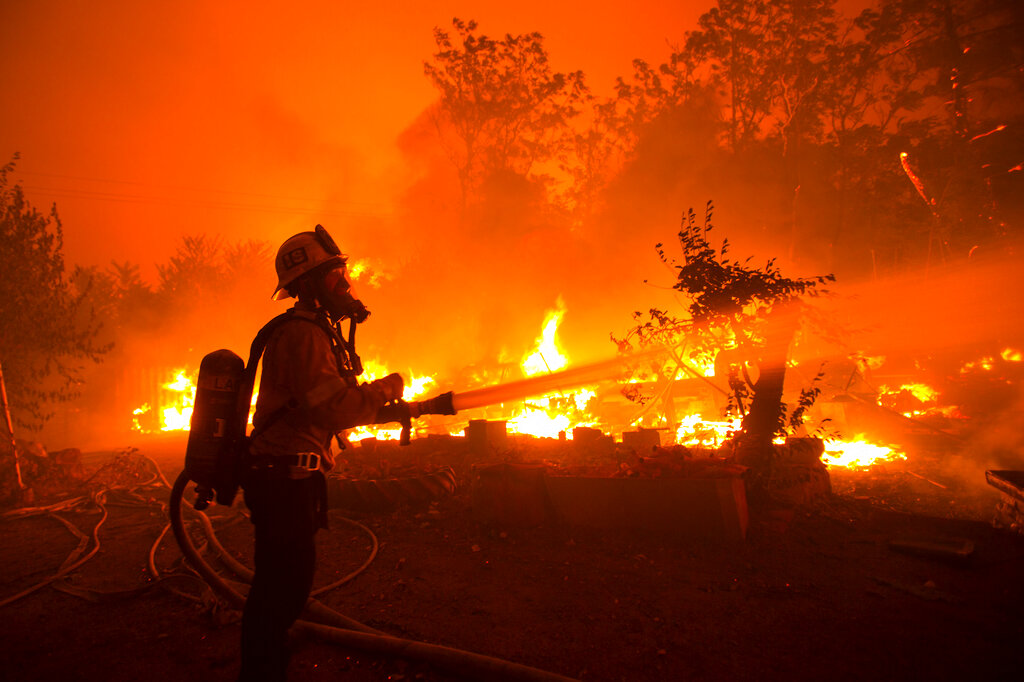 Firefighter put water on flames at California wildfire