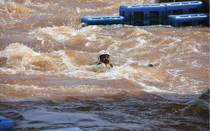 If a rescuer accidentally falls into the water, he must maintain proper body positioning and control until he can find a way out of the water. Notice that his head is up, he's looking for hazards and escape routes as he moves downstream, and he's keeping his feet up to avoid foot entrapment.
