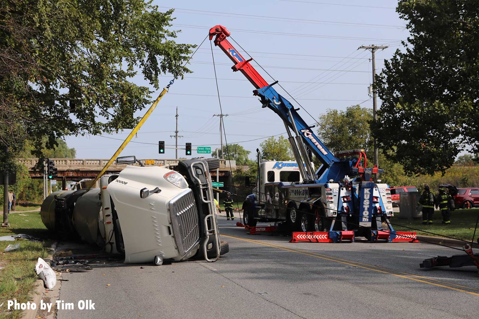 A crane truck lifts the rolled tanker truck