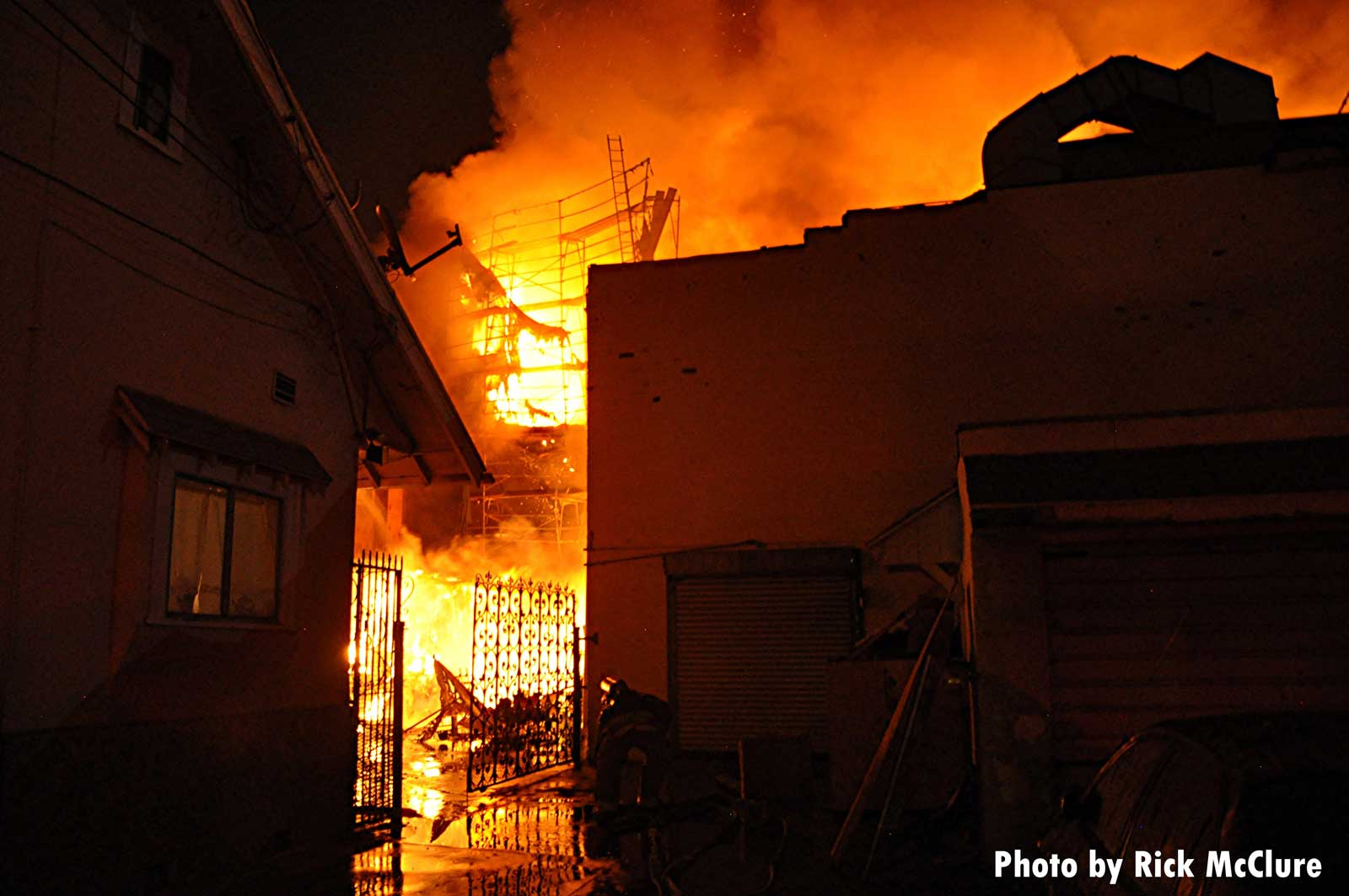 Flames roaring behind a structure in East L.A.