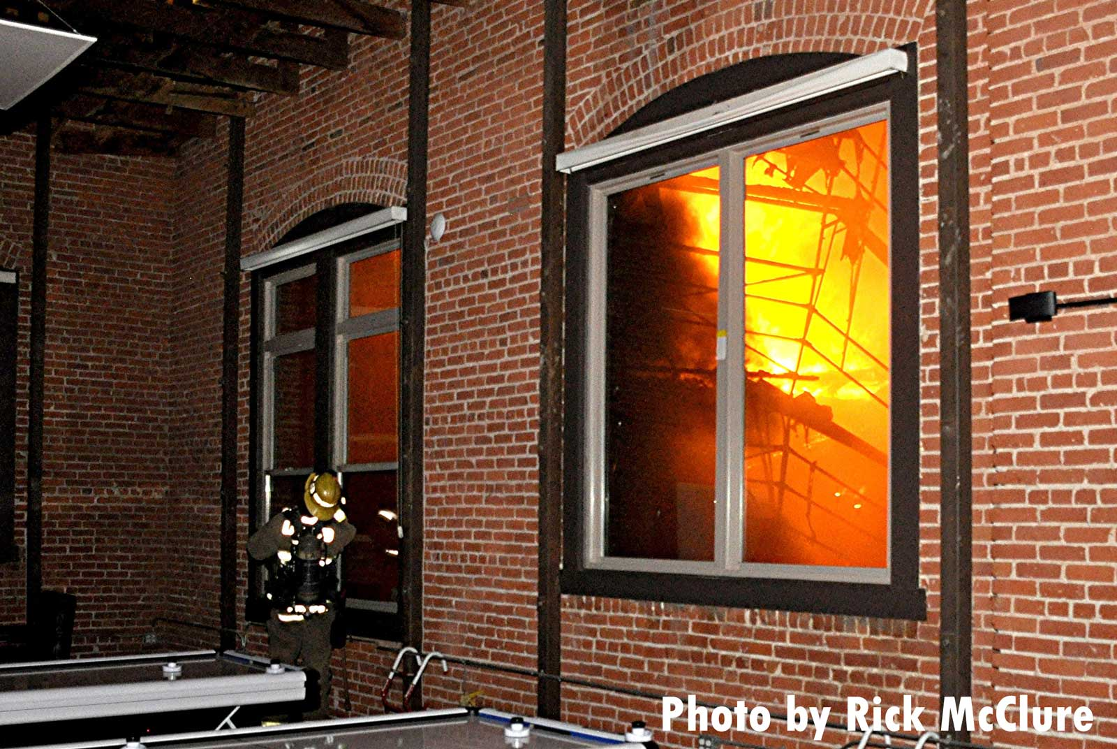 A firefighter with flames seen in the window