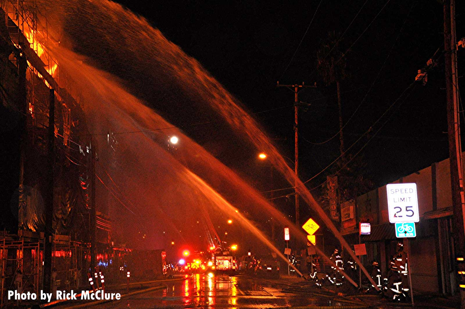 Firefighters train multiple hose streams on the flames