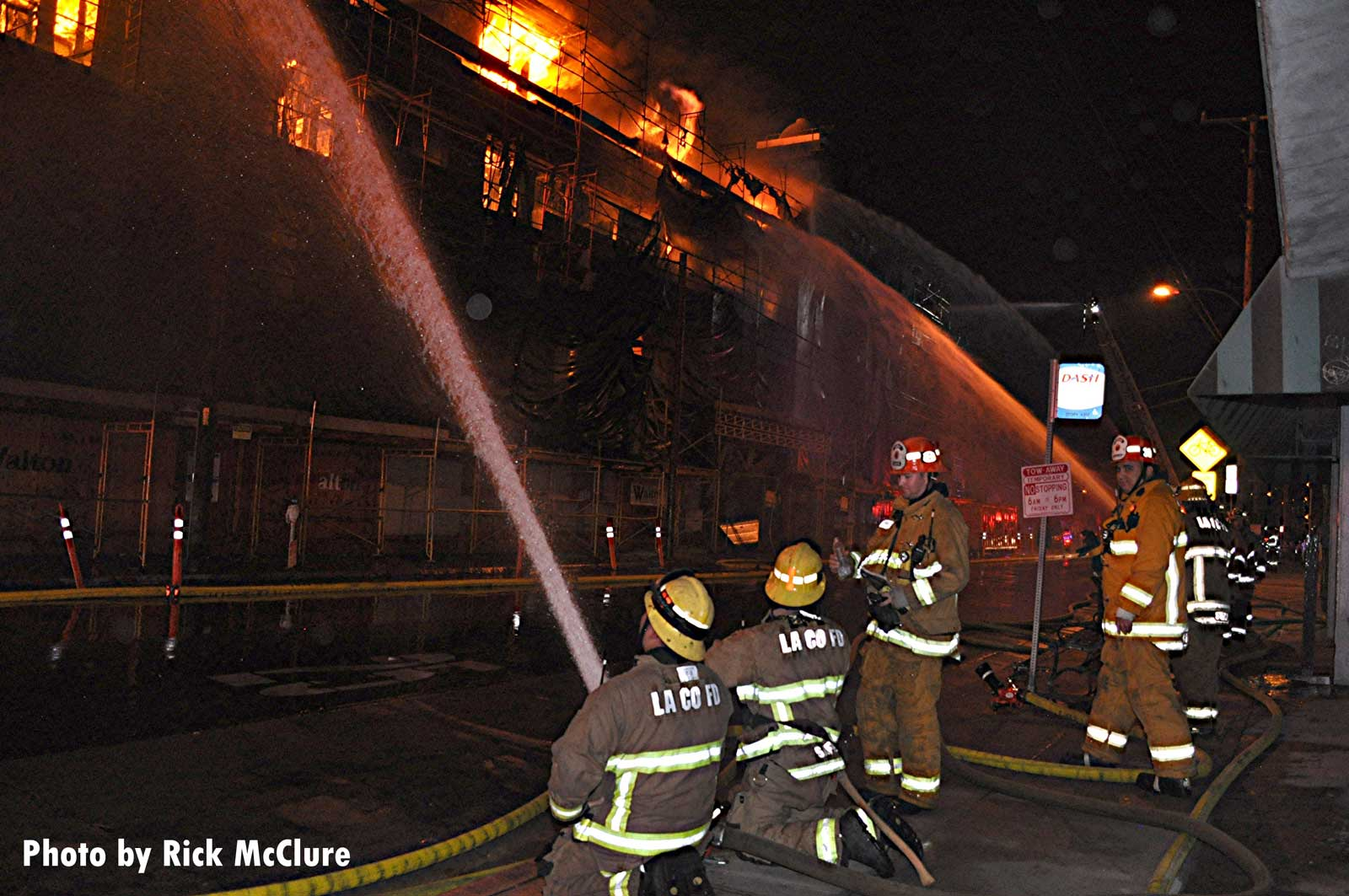 Firefighters with hoselines at the fire