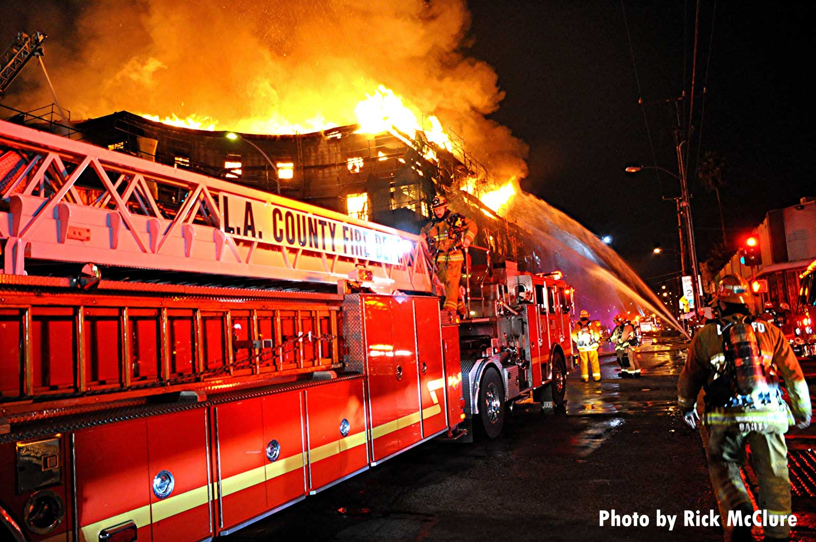 Ladder truck with flames shooting from the building