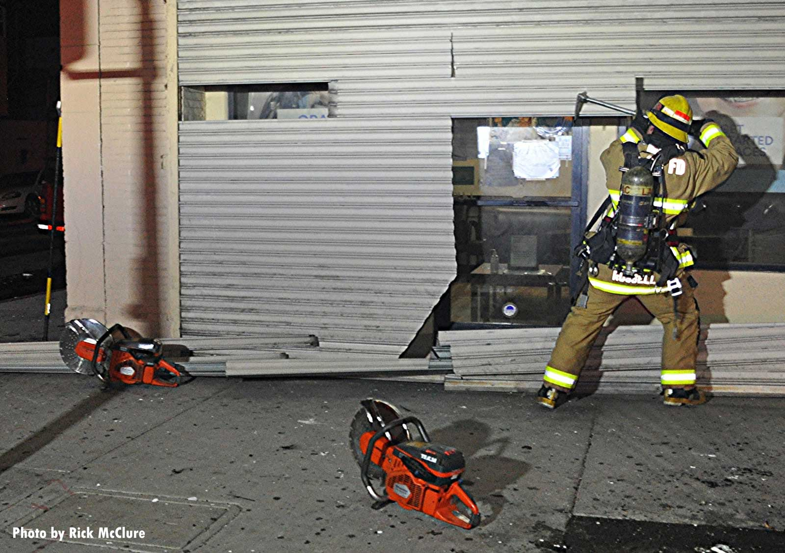 Firefighte rmaking multiple cuts in metal roll-down gate for forcible entry at fire