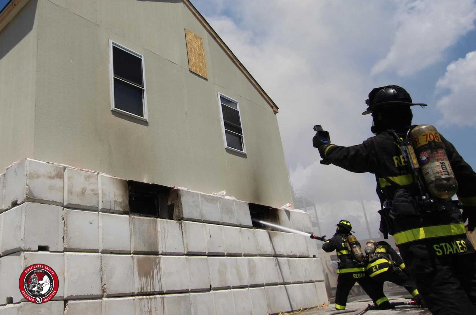 Firefighter with a TIC on exterior of structure while firefighter puts hose stream through opening