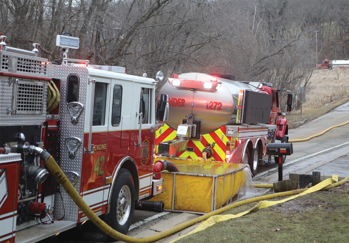 The first-arriving tender established a nursing operation on the roadway in front of the fire scene.