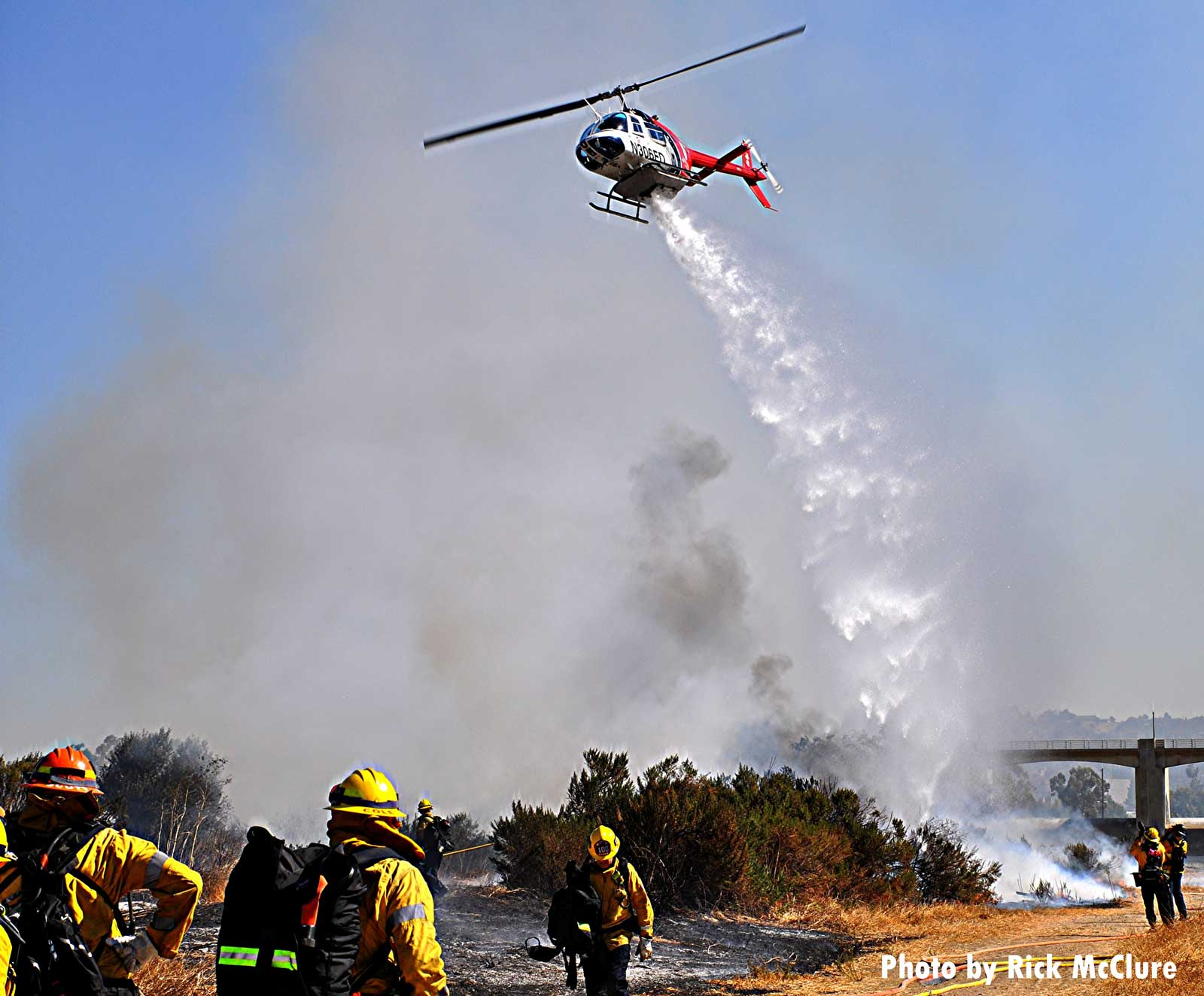 Firefighters observe helicopter making a drop on vegetation fire