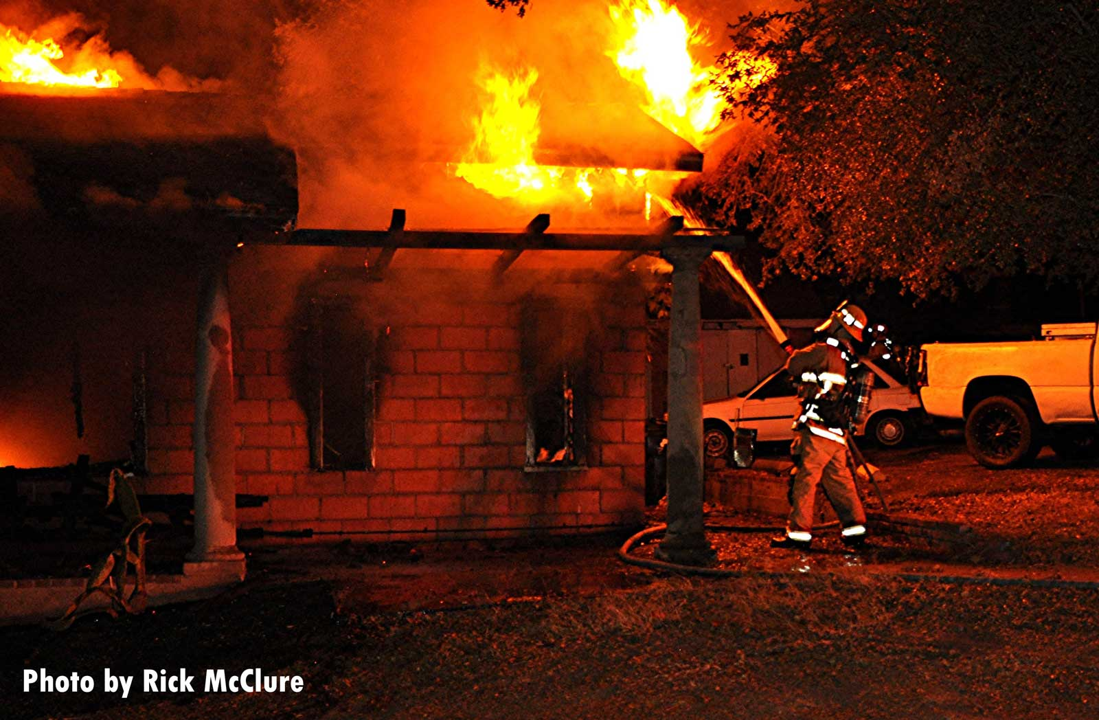 LAFD firefighter applies water on flames shooting from a home