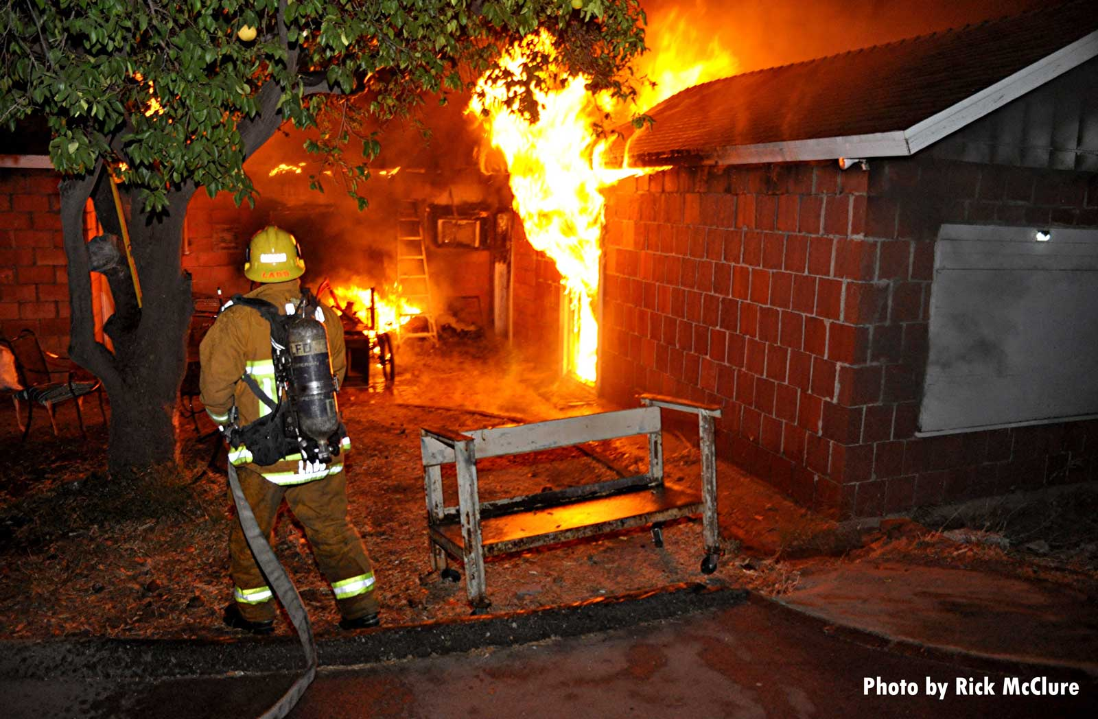 A firefighter with an uncharged hoseline observes raging house fire