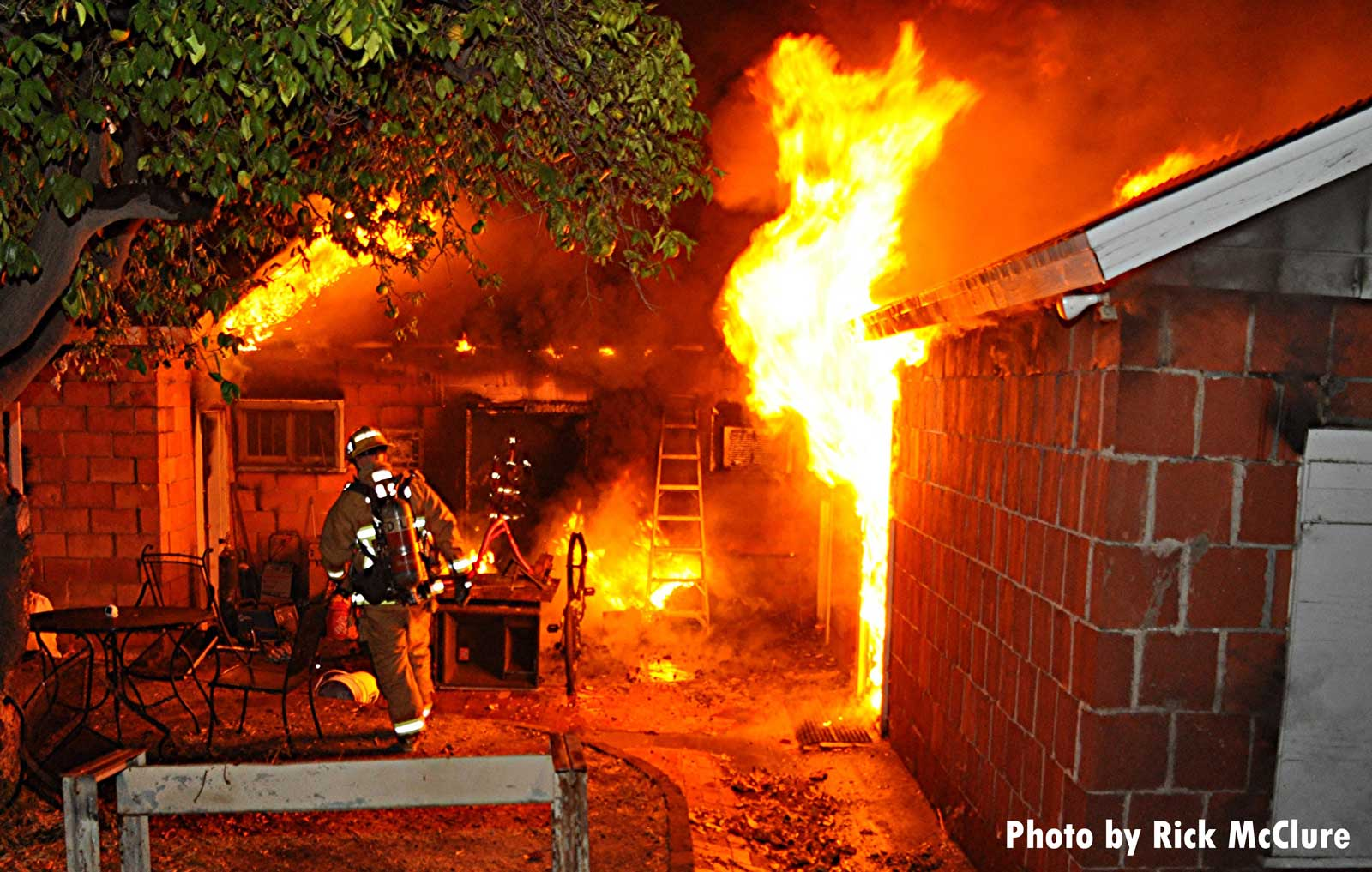 A firefighter at work as flames shoot from a structure