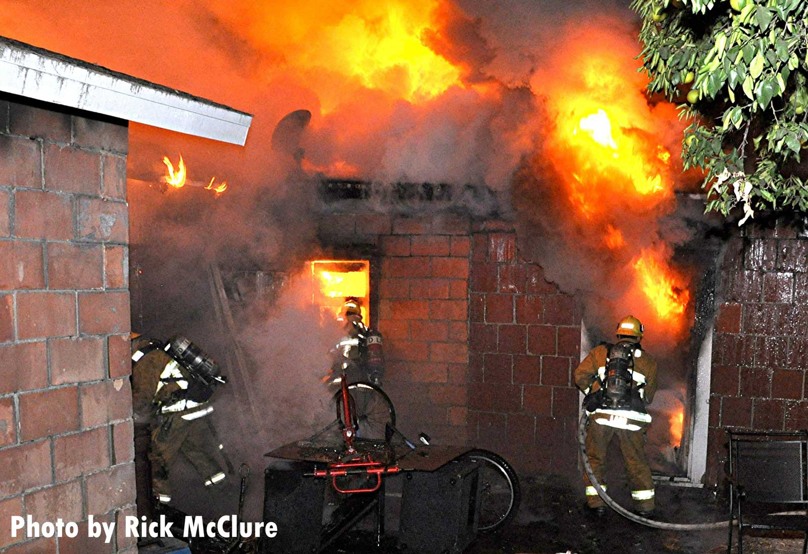 Raging flames shoot from a home as firefighters work to control a Tujunga fire