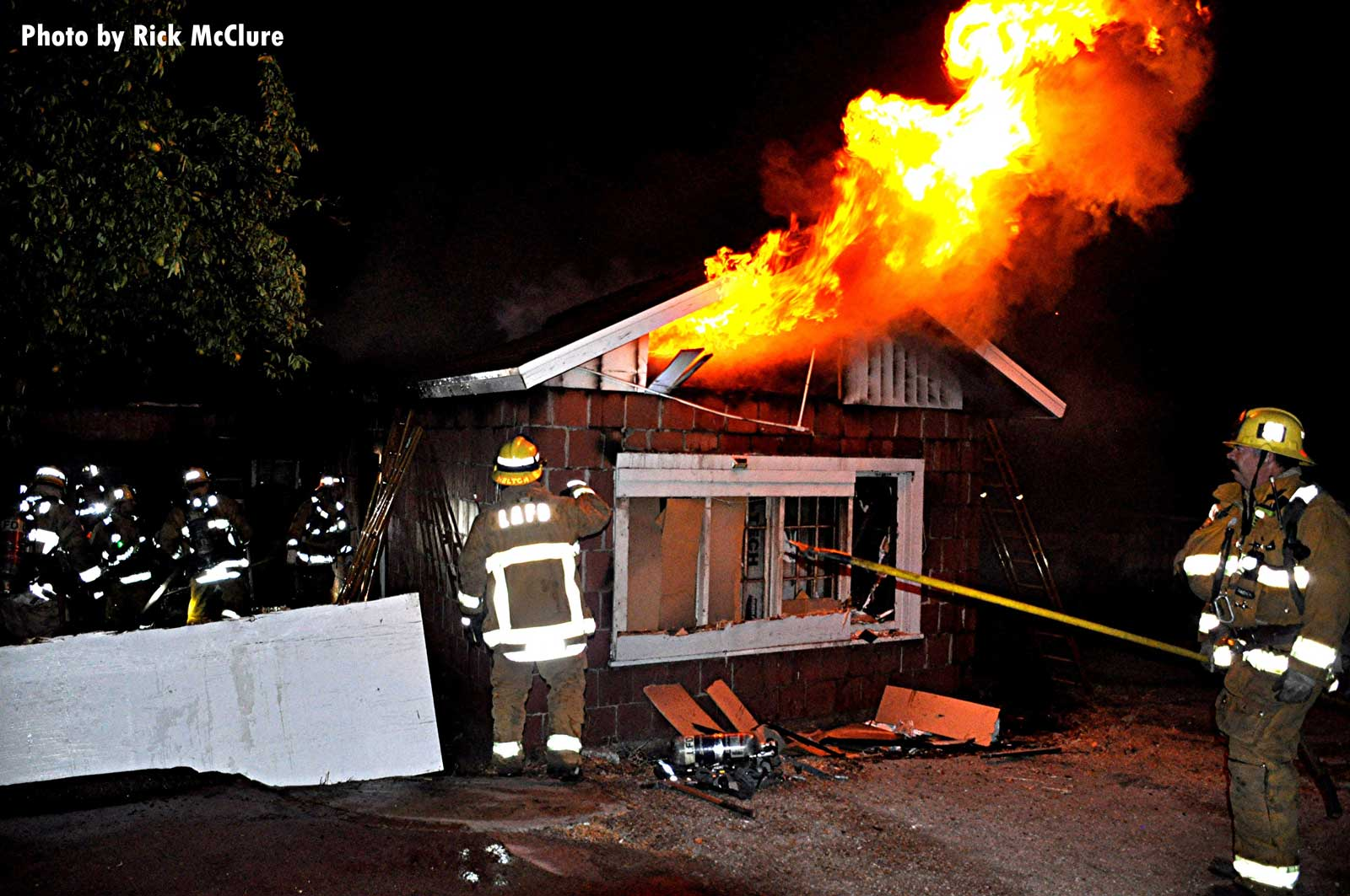Flames shoot out from under the roof of the fire