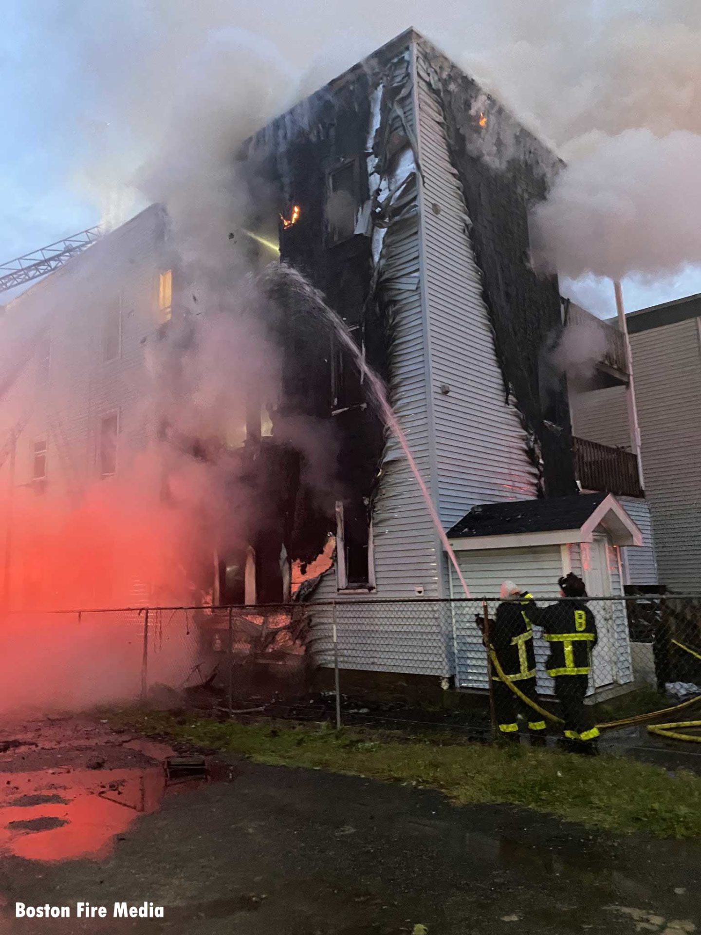 Firefighters apply water on the charred building exterior