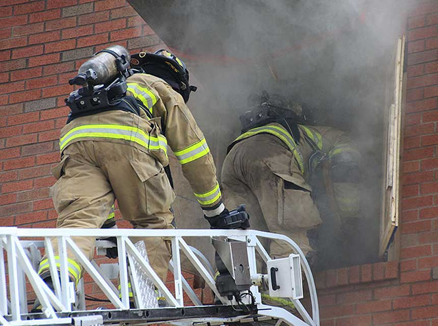 Firefighters enter a building via an aerial ladder during training at FDIC International