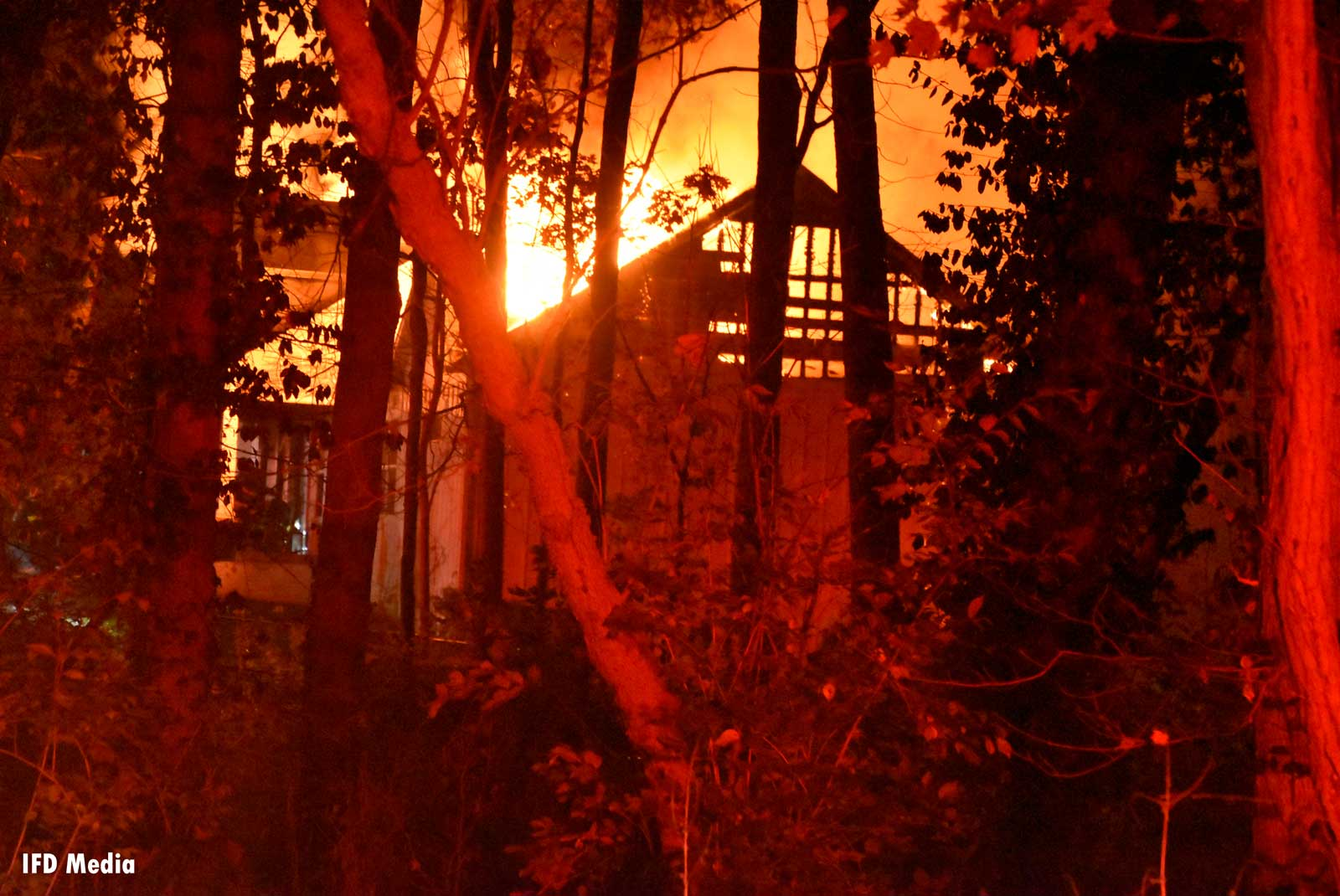 Burning home glimpsed through trees
