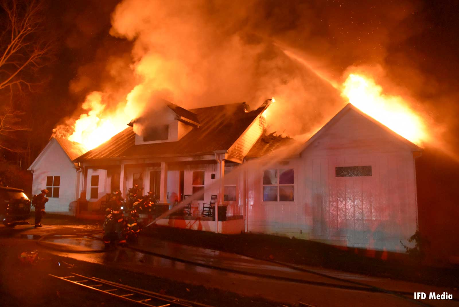 Firefighters put hoseline on the outside of a building