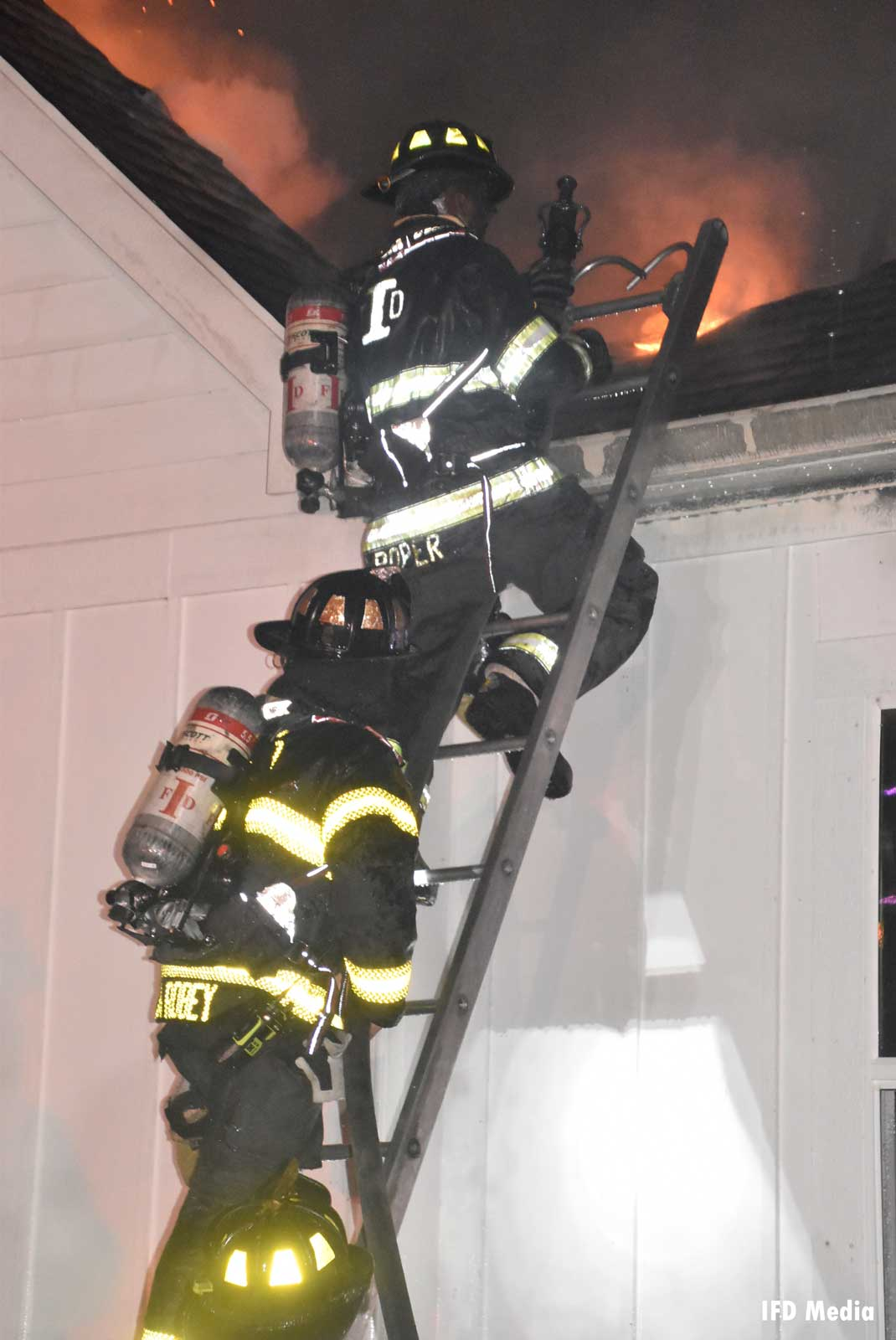 Firefighters ascend a ladder to roof of burning home