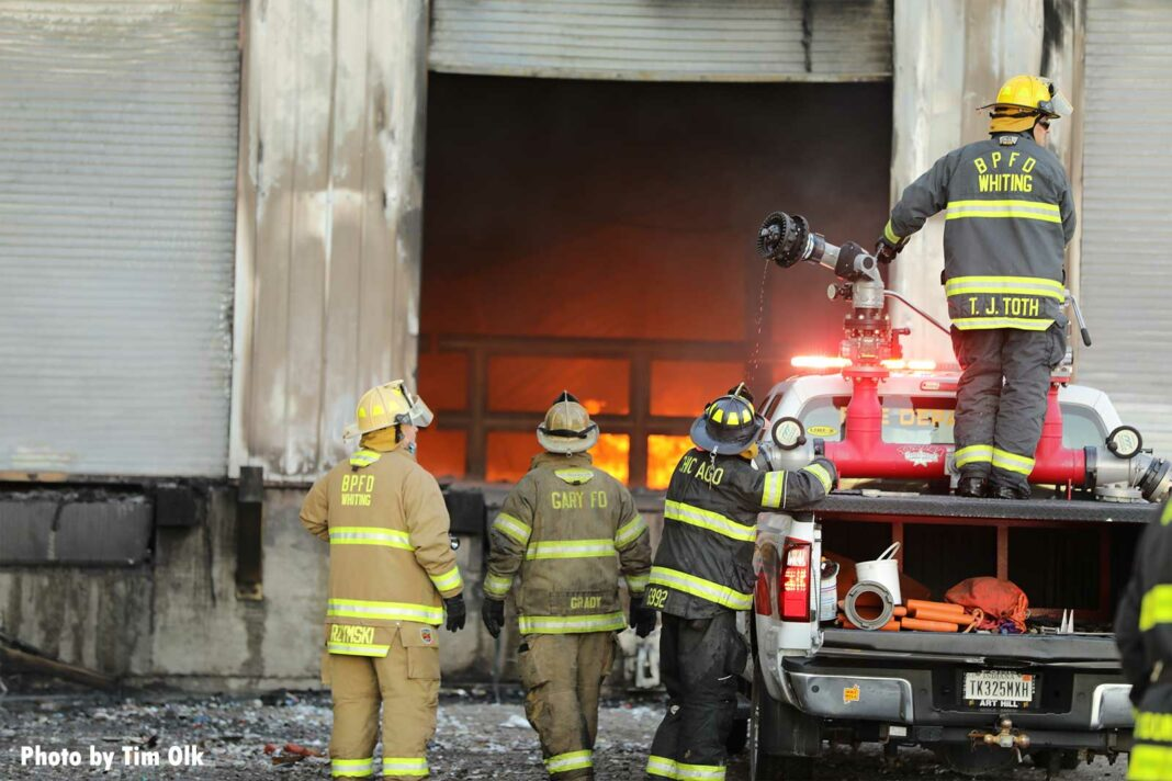 Firefighters prepare to attack fire through roll-down doors
