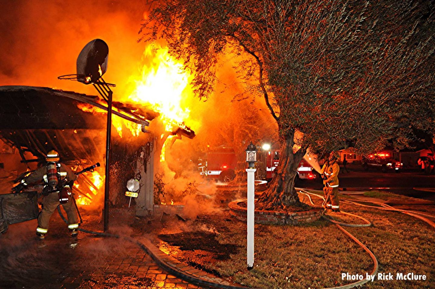 Flames lick up at tree as firefighters respond to burning building with a basketball hoop
