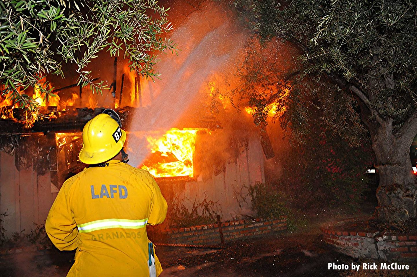 LAFD firefighter directs hose stream onto heavily involved building
