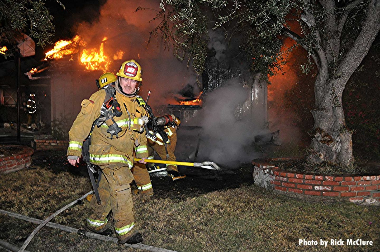 Firefighter with a hook walking with flames on roof of building
