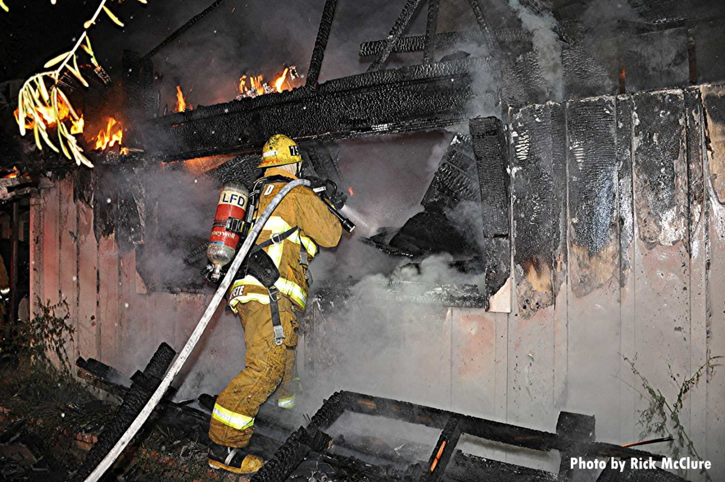 Firefighter directs hose stream through window as fire burns in structure