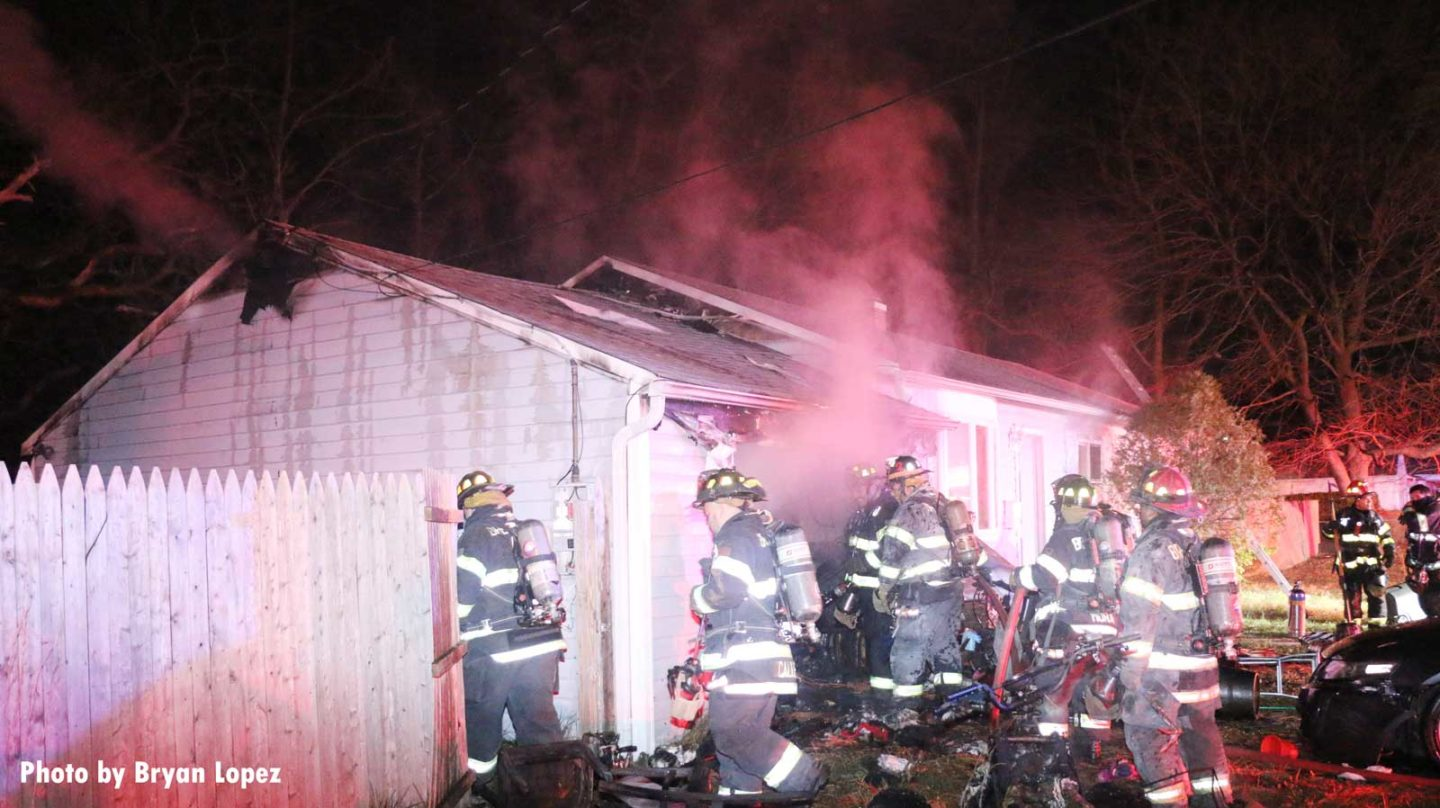 Firefighters move around a burning home during fireground operations