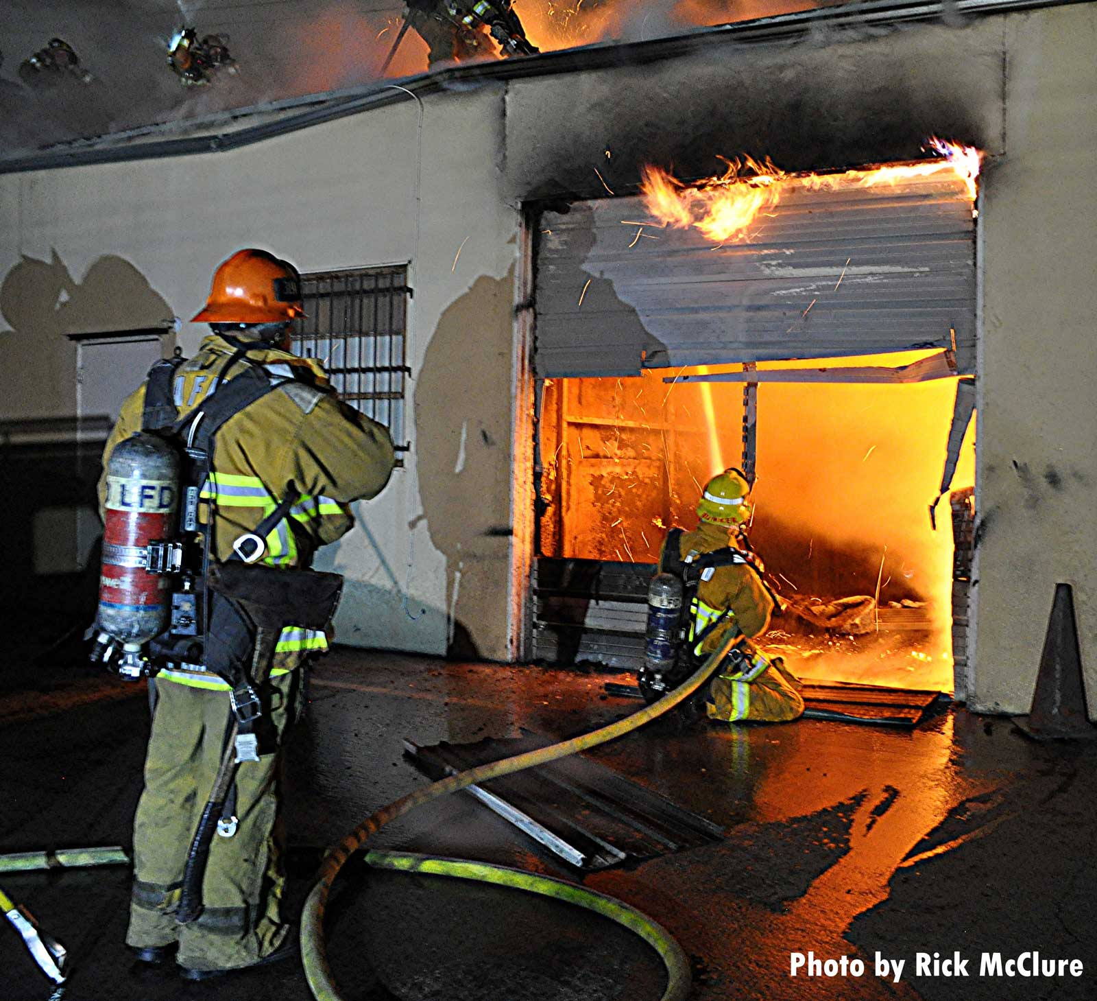 A kneeling LAFD firefighter with a hoseline sprays water on flames through a cut roll-down door