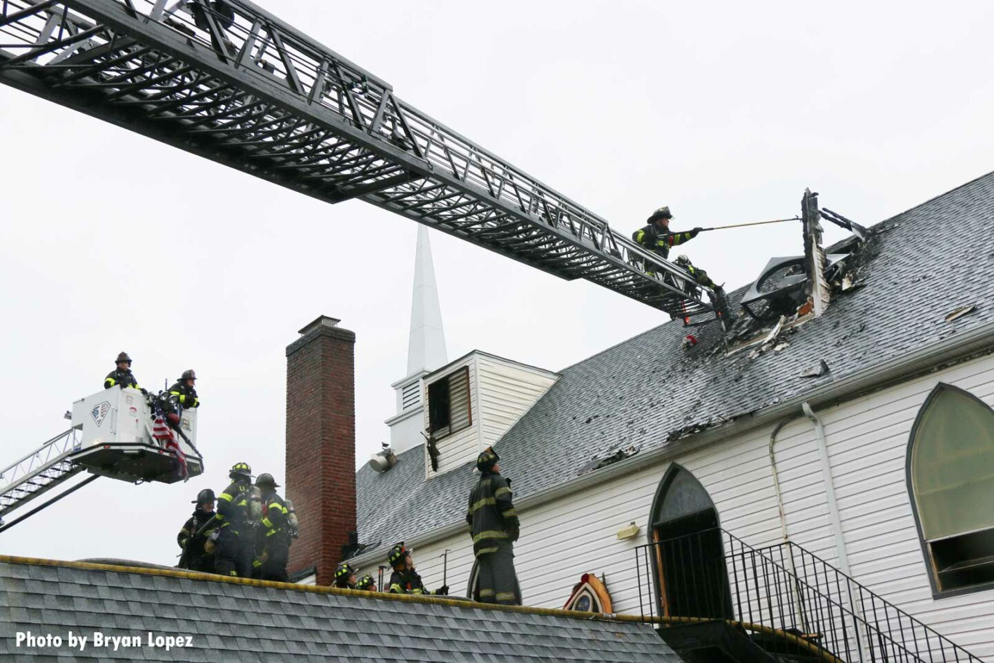 Aerial device extended to roof of church with firefighter working