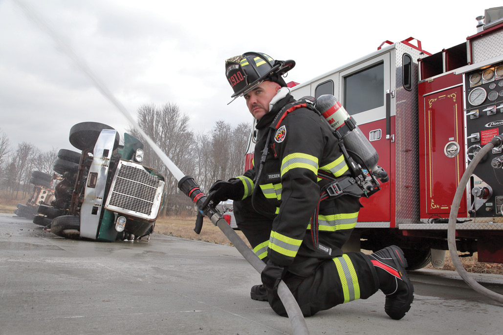 Firefighter in gear with an apparatus flowing water