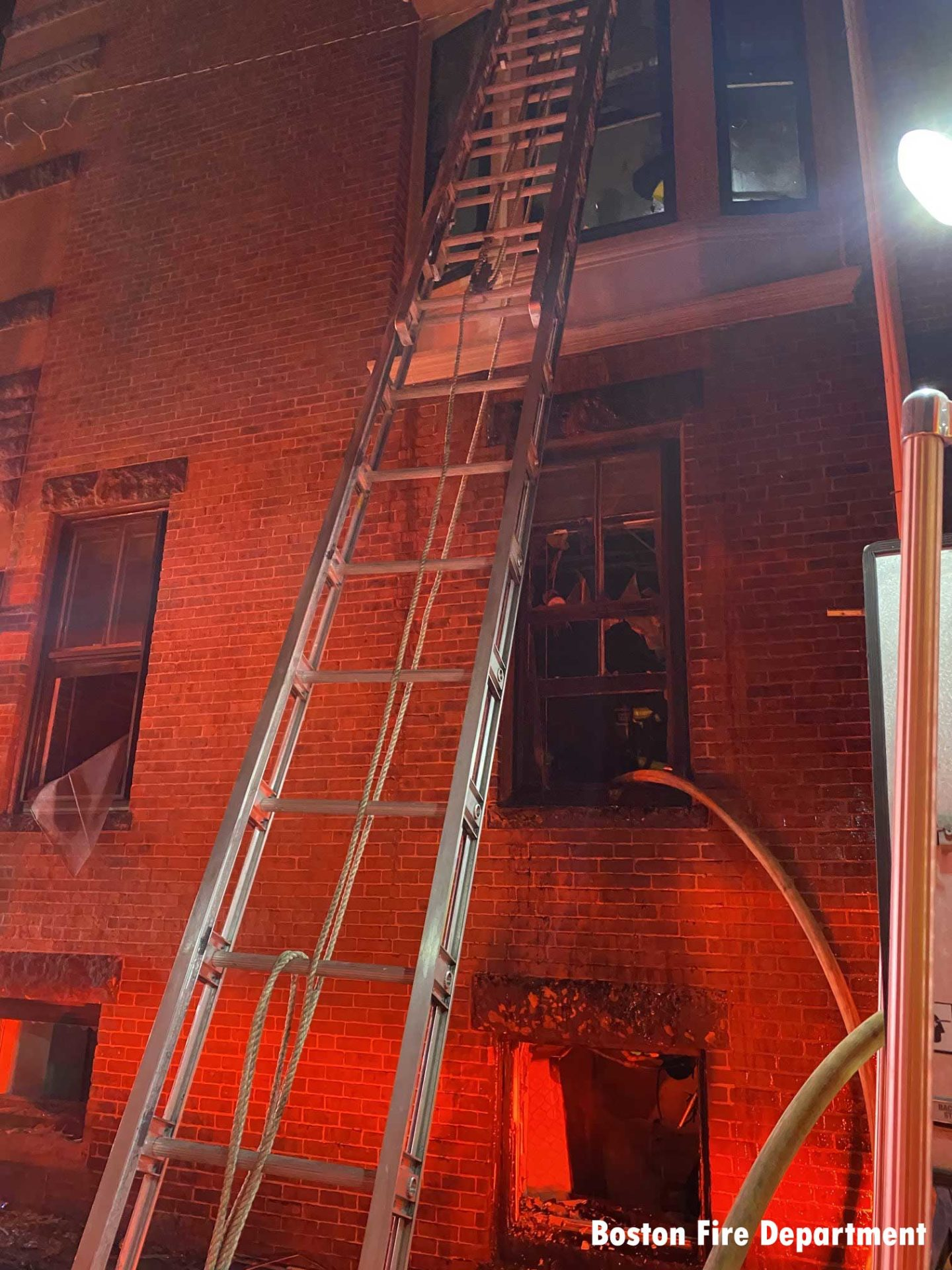 Ladder raised with hose through the window