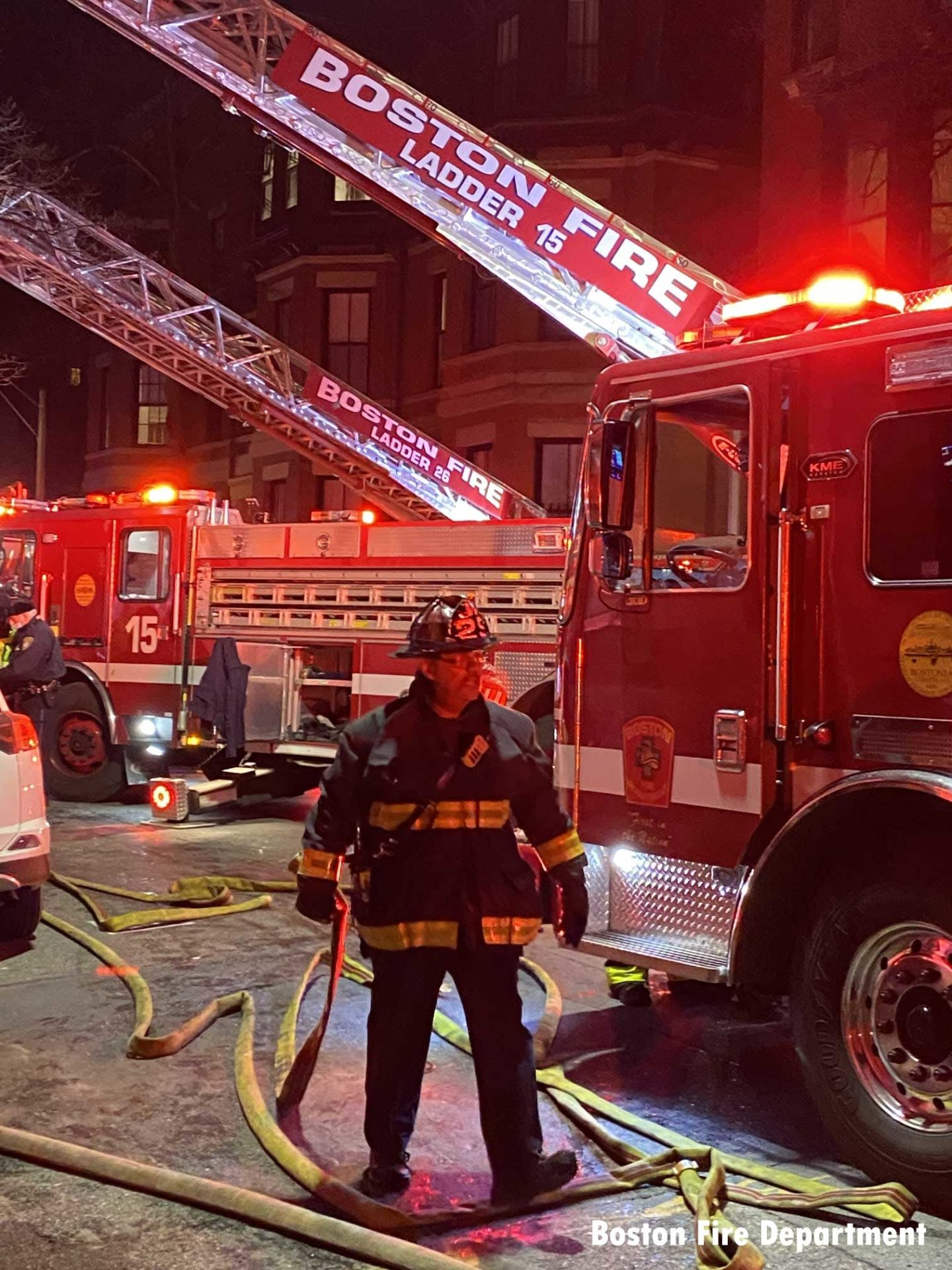 Boston firefighter with hoseline and two aerials raised