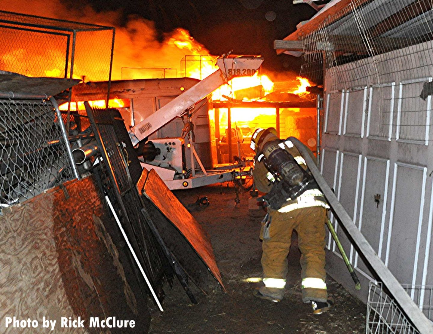 Firefighter hauls a charged hoseline between structures