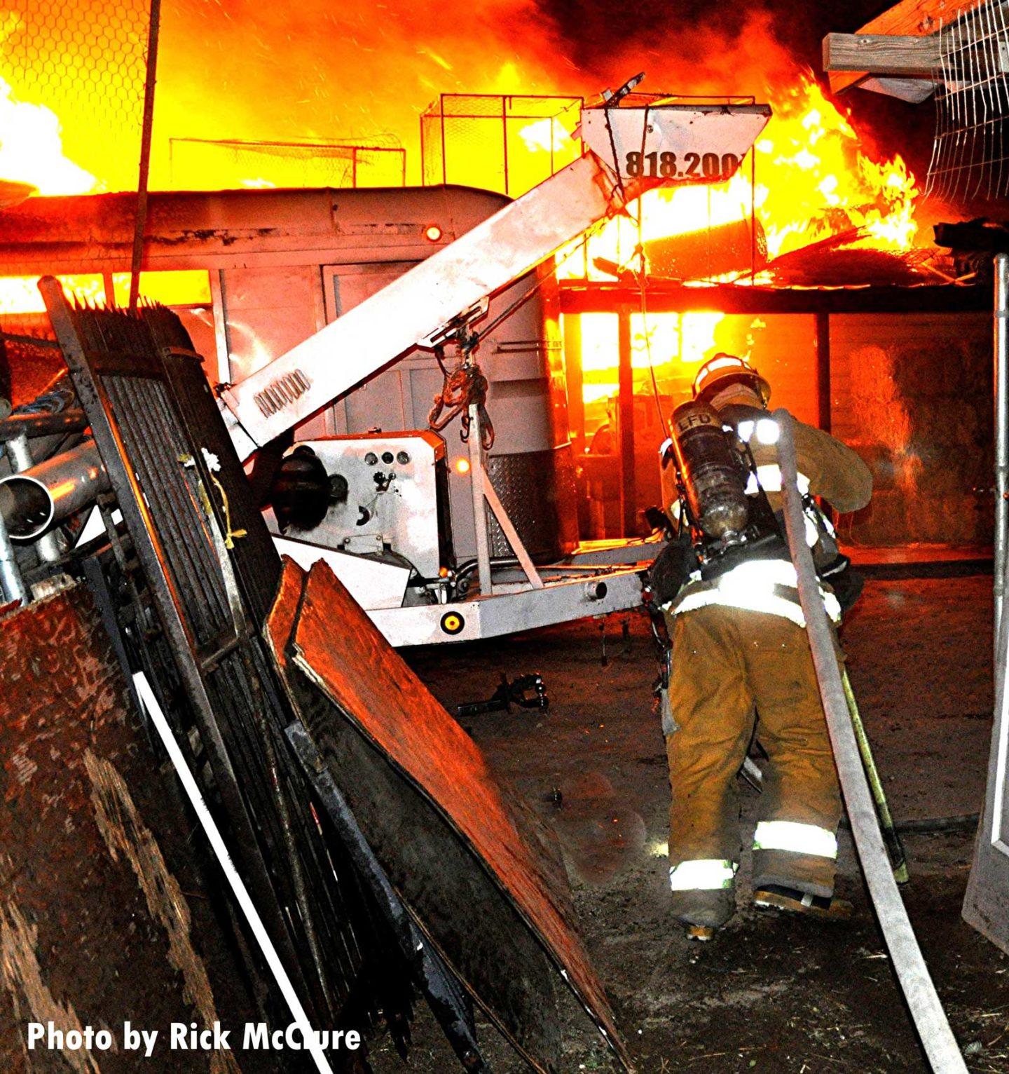 A firefighter pulls a hoseline toward massive flames
