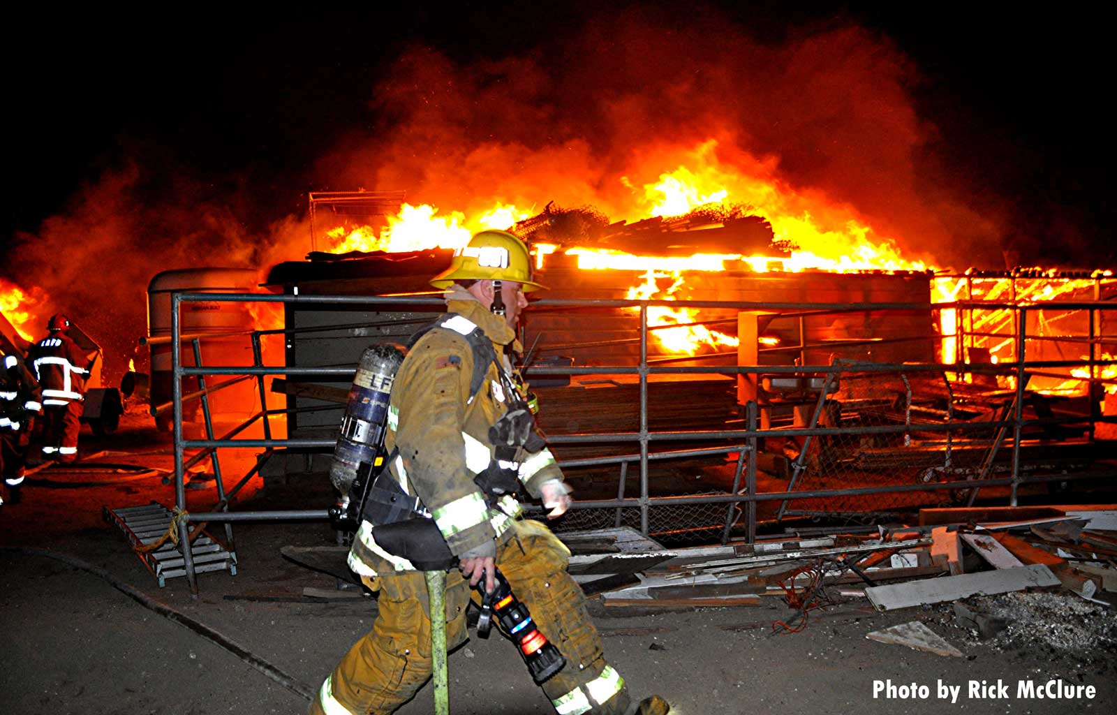 A firefighter strides past a burning pile of debris