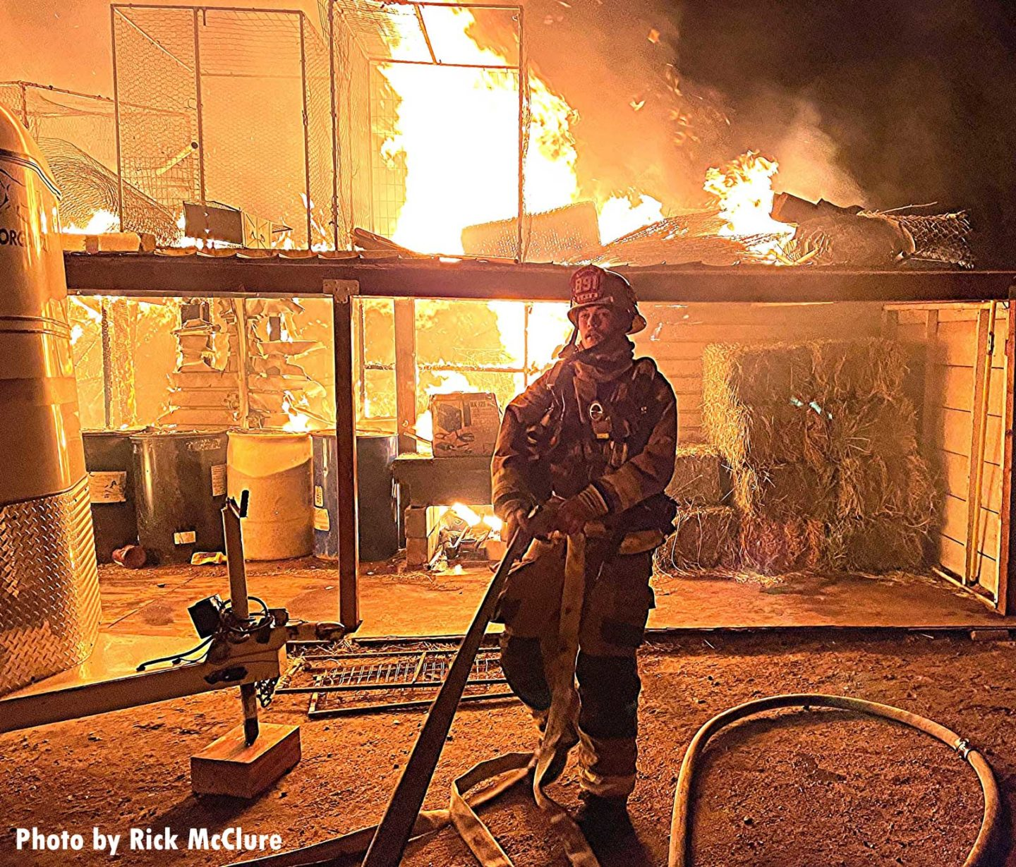 Firefighter flakes out a hoseline with flames in the background