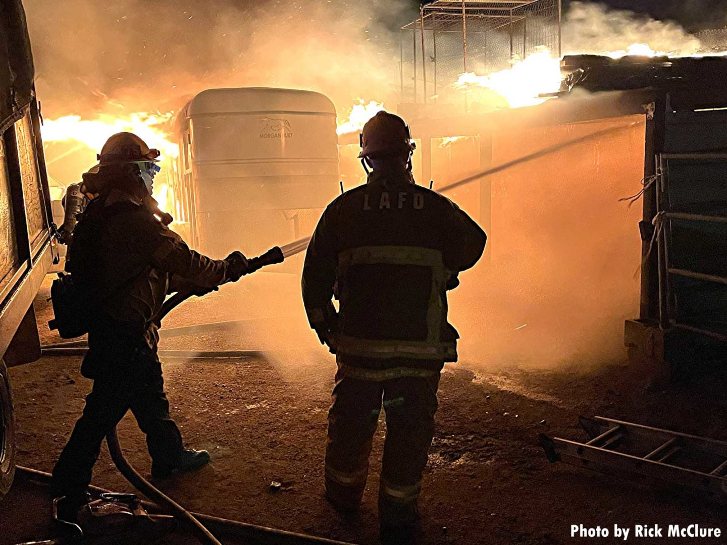 Firefighters with hose putting water on flames