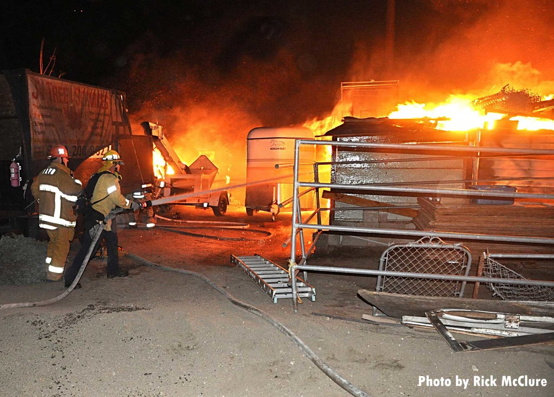 Two firefighters train hoseline on burning object