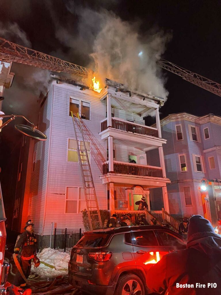 Multiple aerials in use as flames shoot from the top of the dwelling and a ground ladder on the building