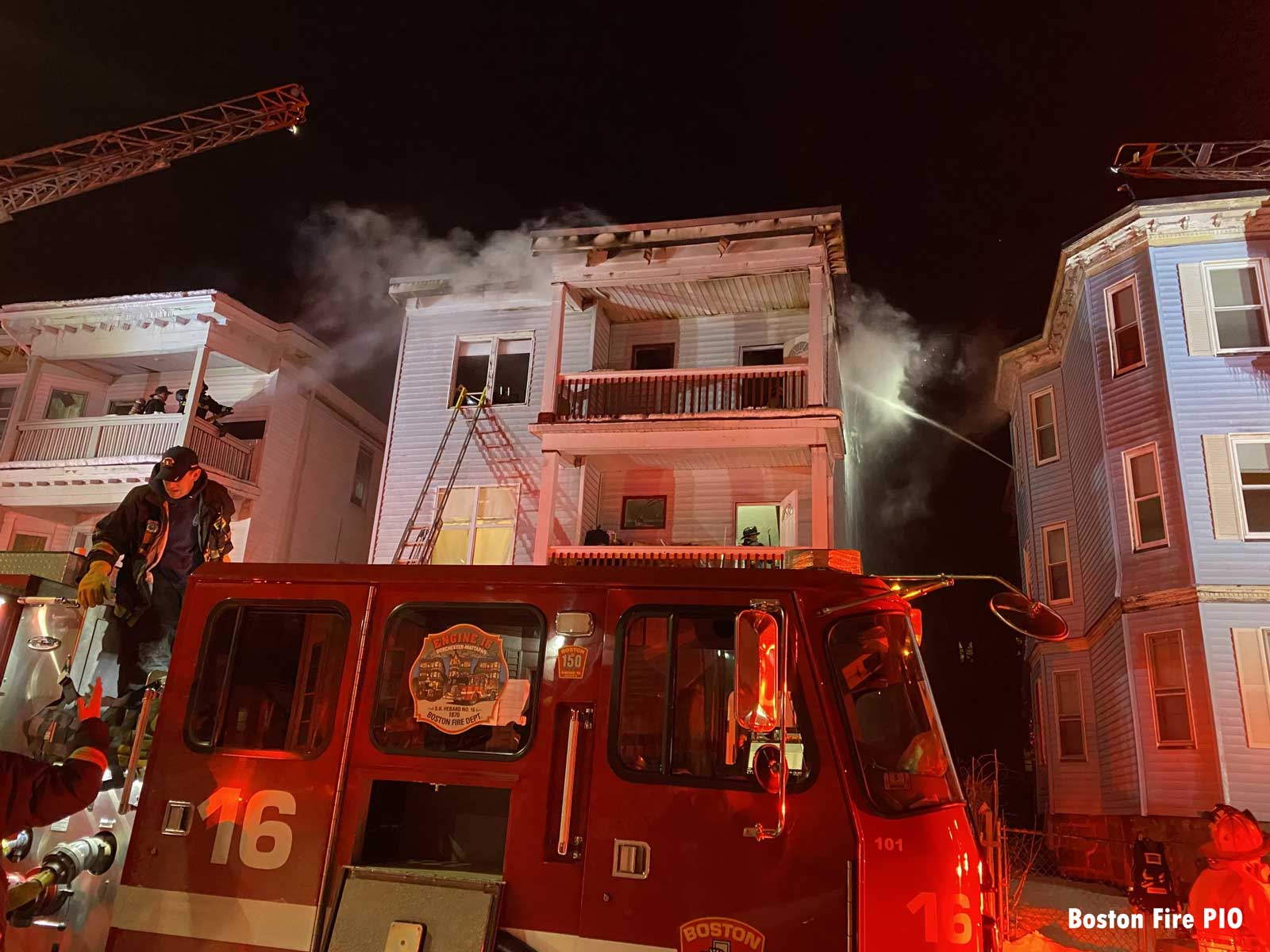 Firefighter on a fire truck with fire building behind and two aerials in use in Boston