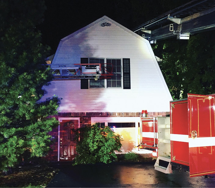 The tower ladder was backed into position so the crew could work out of the bucket and perform operations on this gambrel-shaped roof.