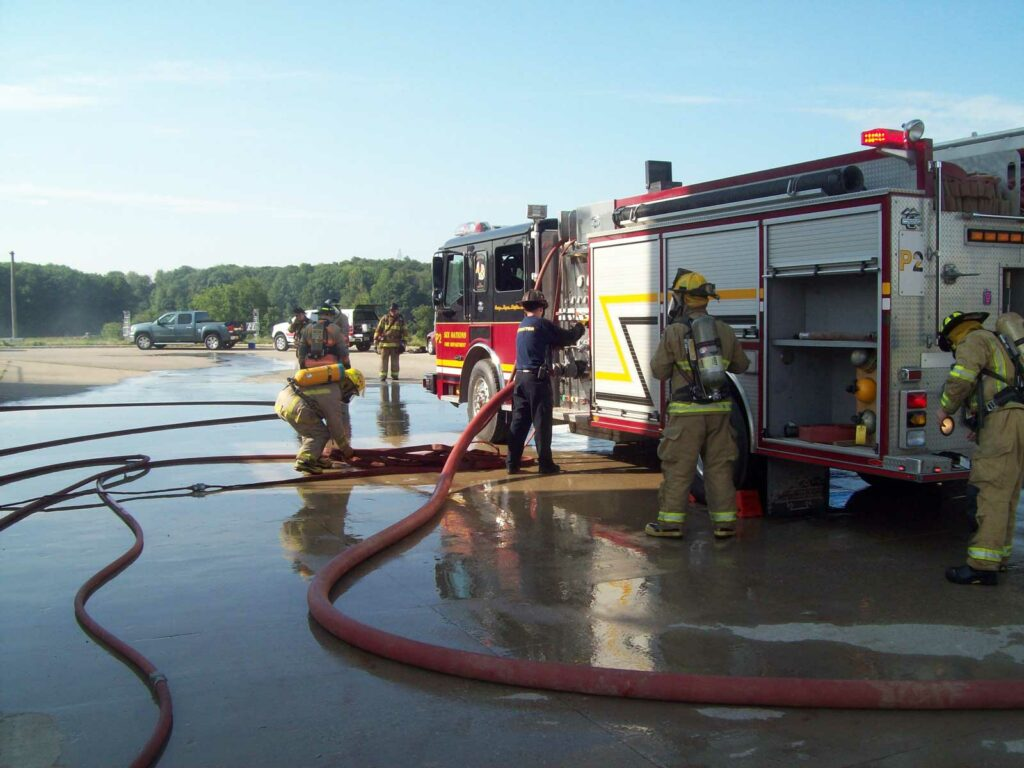 Firefighters pumping water on a fire apparatus