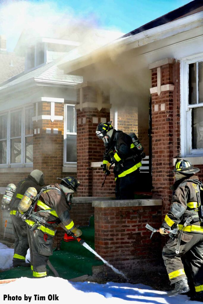Firefighter tests flow of handline prior to making interior push at house fire